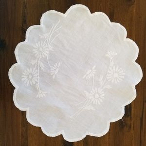 Vintage scalloped doily with embroidered daisies